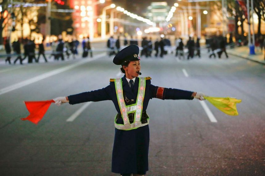 A policewoman controls the traffic as people gather near the main Kim Il Sung square in central Pyongyang, North Korea April 11, 2017.