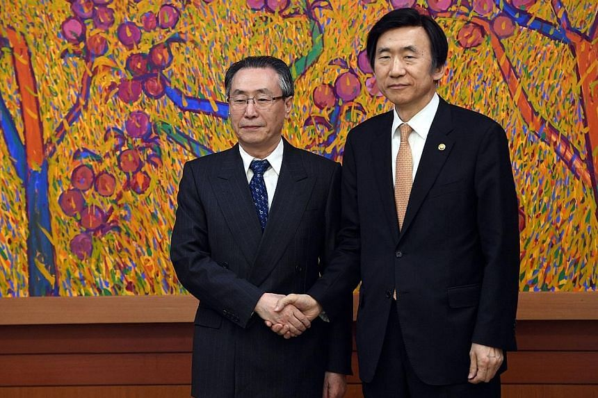 South Korean Foreign Minister Yun Byung Se (at right) with China's Mr Wu Dawei during their meeting in Seoul yesterday. Mr Wu's trip was the first visit to South Korea by a senior Chinese official after the planned deployment of the US Thaad missile