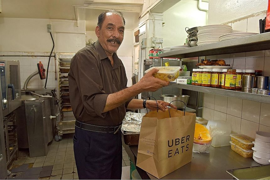Mr Mohammad Rahim Dad Khan Abbasi, a chef at Bismillah Briyani Restaurant, packing food for delivery last Thursday. Since teaming up with food delivery platforms such as UberEats and Foodpanda last September, the restaurant's revenue has gone up 17 p