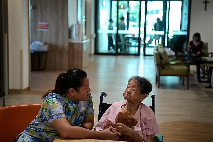 Nurse Joanna Rose Evardone interacting with Madam Liow Ah Tay last week. Madam Liow is among the pioneer batch of patients at Assisi's dementia ward.
