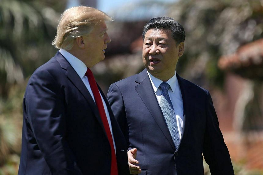 US President Donald Trump and China's President Xi Jinping chatting as they walk along the front patio of the Mar-a-Lago estate after a bilateral meeting, on April 7, 2017.