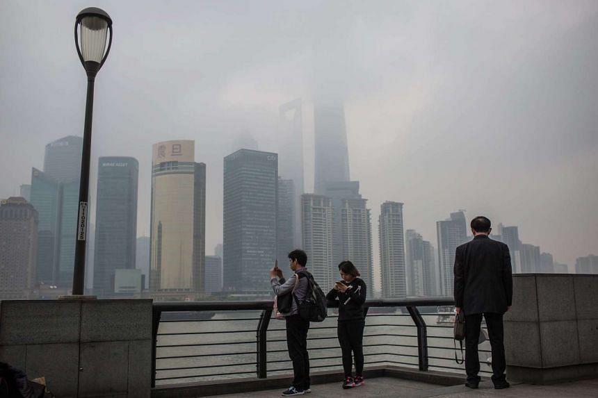 Tourists at the Bund, with the Pudong skyline towers seen through heavy smog during a rainy and polluted day in Shanghai.