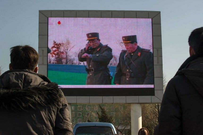 People watching a news footage of a missile launch on a giant television screen outside the main railway station in Pyongyang, on March 7, 2017.