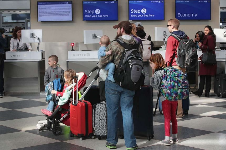 Travellers check in for flights at O'Hare International Airport, on March 14, 2017, in Chicago, Illinois.