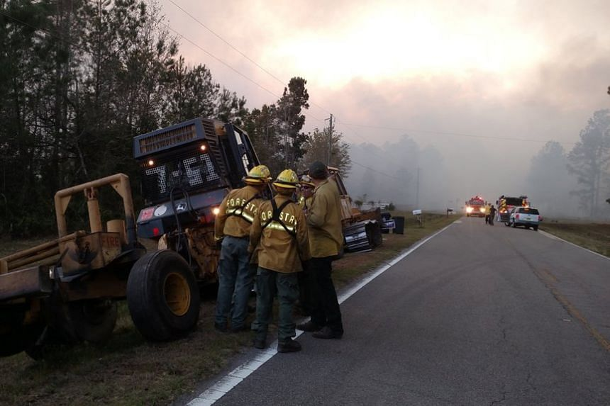 Firefighters deal with a wildfire that quickly spread across acres of land in Florida on March 22, 2017.