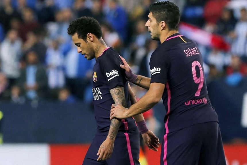 Barcelona's Brazilian striker Neymar (left) reacts next to teammate Luis Suarez during the match against Malaga.