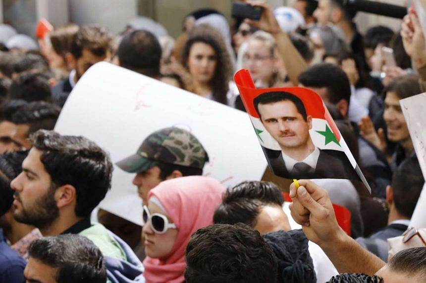 Syrian protesters wave a flag bearing a portrait of their country's President Bashar al-Assad during a demonstration in his support outside the United Nation's office in the capital Damascus, on April 11, 2017.
