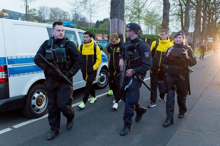 Borussia Dortmund players (from left) Nuri Sahin, Marcel Schmelzer and Sven Bender are escorted by police after the incident.