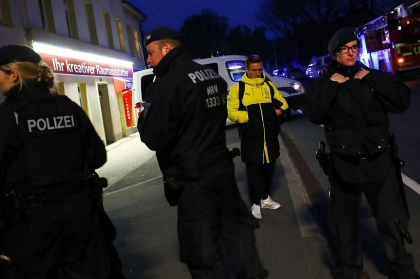 Borussia Dortmund's Felix Passlack with police after the explosion.