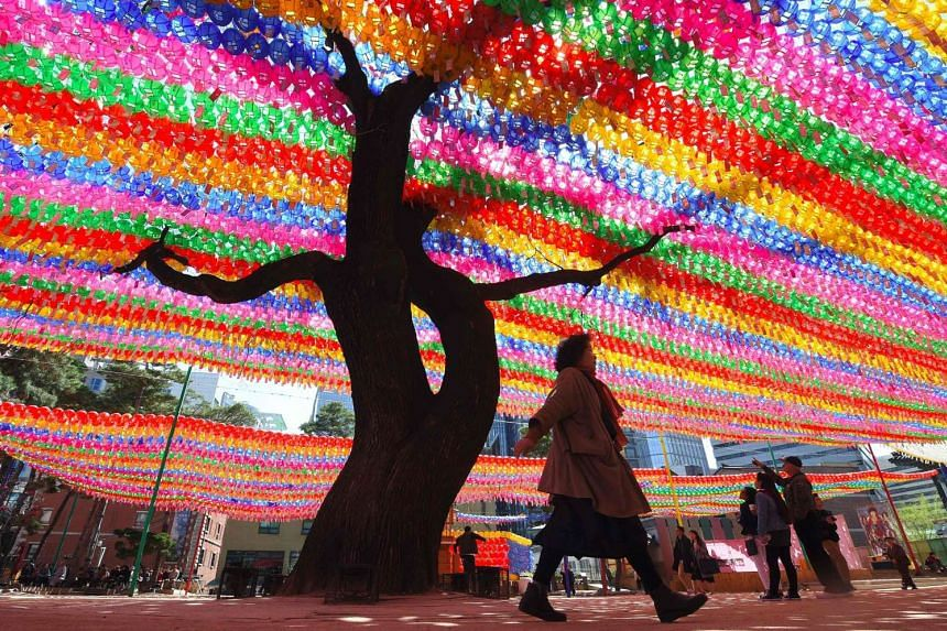 A woman walks past a tree decorated with lotus lanterns at Jogye Temple in Seoul.