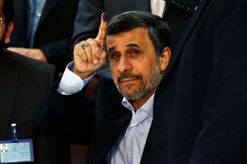 Former president Mahmoud Ahmadinejad shows his inked finger after registering his candidacy.