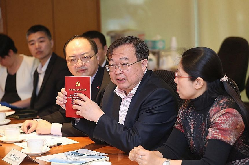 Mr Liu Jianchao with a book on law and regulations issued to Communist Party members. He was speaking to journalists from Singapore Press Holdings yesterday.