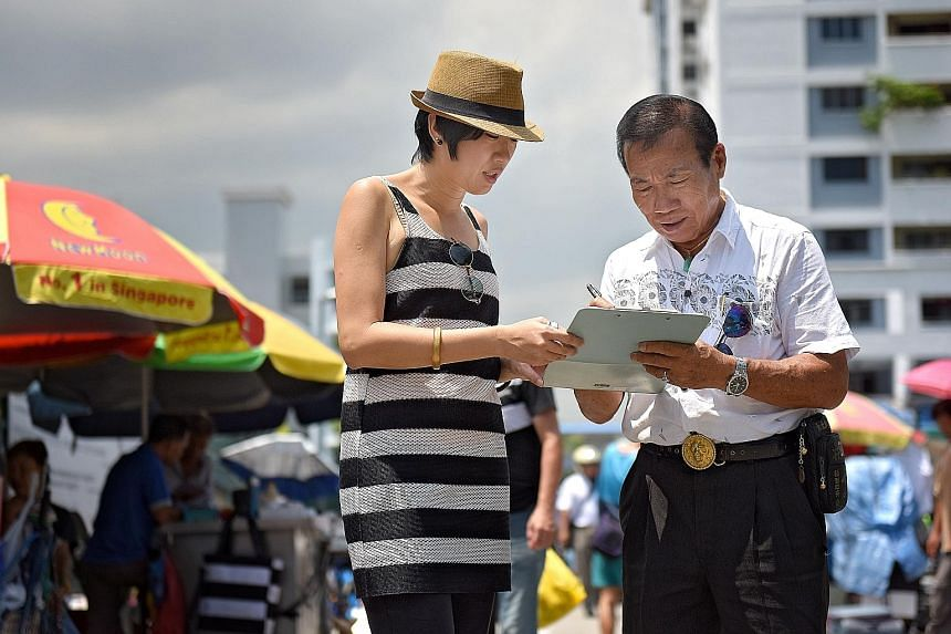 Save Sungei Road Market group's Ms Tan Biyun getting a signature from Mr Koh Ah Koon, president of the Association for the Recycling of Second Hand Goods. The group aims to get 1,000 signatures for its petition and is looking for a sympathetic MP to