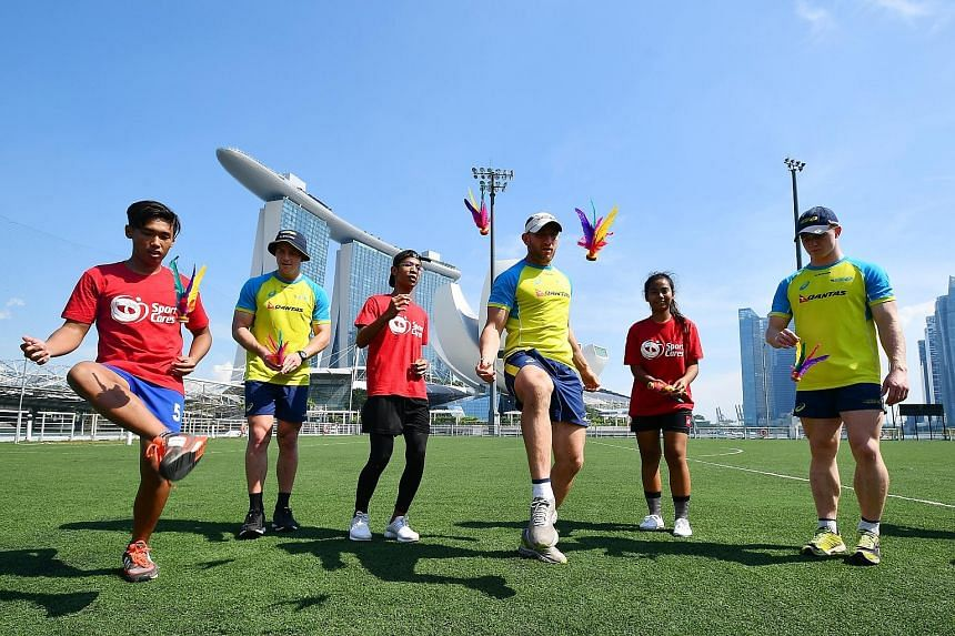 Australia's Rugby Sevens players (from left, in yellow jerseys) Nick Malouf, James Stannard and Henry Hutchison learnt to play chapteh from SportCares participants (in red) Zulkilfli Najib, Dinie Irfan Abdul Raup and Noorisha Elfira Helmy. They were