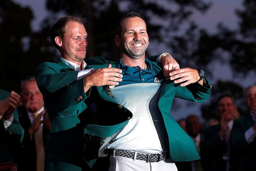 Last year's Masters champion Danny Willett helping Sergio Garcia put on the green jacket after the Spaniard's play-off win at Augusta.