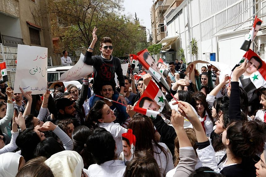 Syrian university students staging a protest yesterday in front of the United Nations office in Damascus against the US missile strike on a Syrian airbase last Friday.
