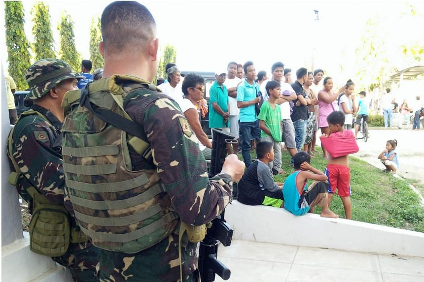 Soldiers stand guard next to residents during a military operation against the Abu Sayyaf in Bohol.