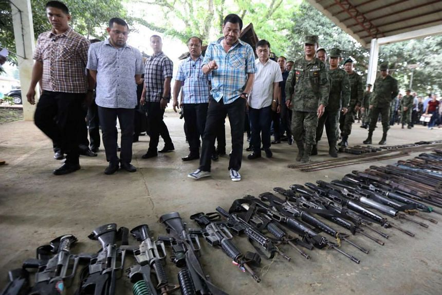 Philippine President Rodrigo Duterte inspecting firearms seized from Abu Sayyaf militants last Thursday. The group, which has sworn allegiance to ISIS, has become better known for banditry.
