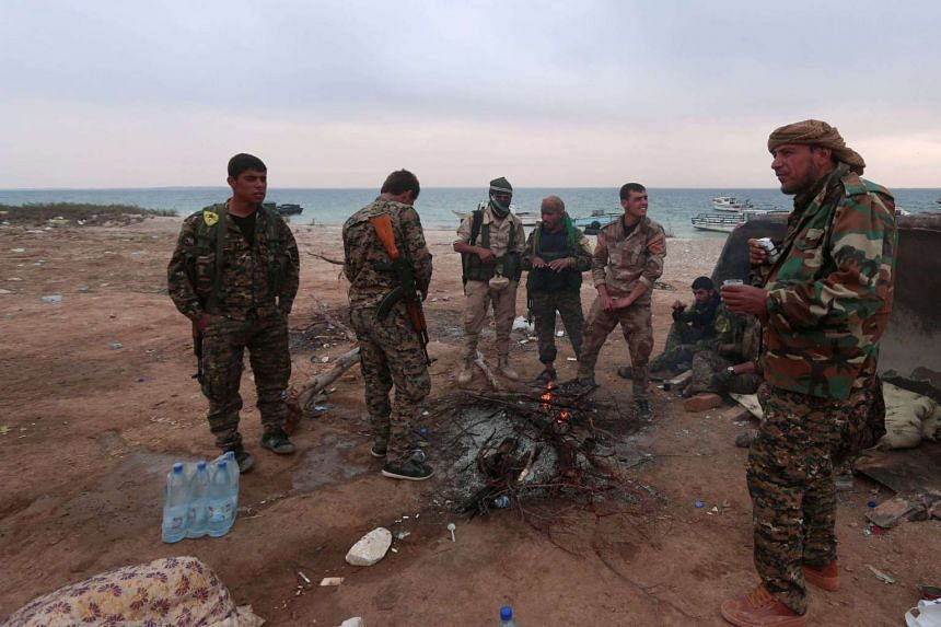 """Syrian Democratic Forces (SDF) fighters on the bank of the Euphrates river. The Pentagon said the air strike landed on a """"forward SDF fighting position""""."""
