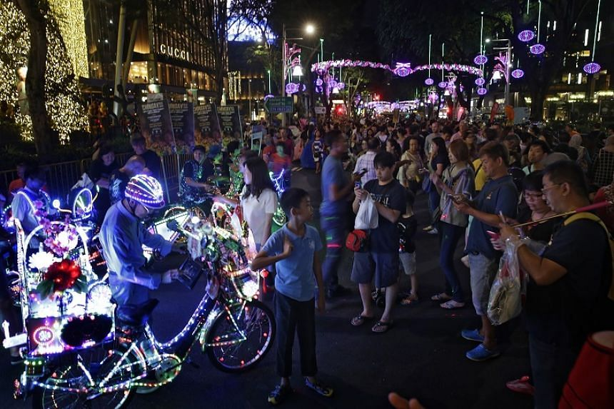 Cyclists parade their decorated electric bicycles alongside other performers from People's Association to promote Chingay during Pedestrian Night in Orchard Road on Jan 2, 2016.