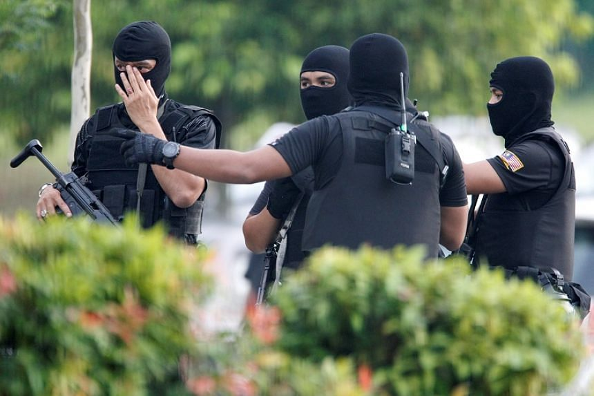 Armed policemen stand guard before the arrival of suspects charged with the murder of Kim Jong Nam, at a Sepang court.