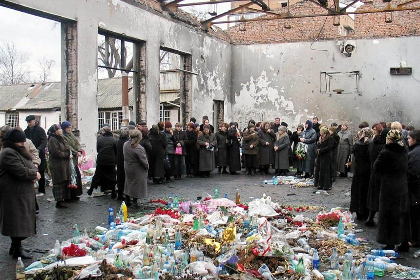 Friends and relatives of the victims of the Beslan massacre hold a minute of silence to commemorate the six-month anniversary of the tragedy on March 3, 2005.