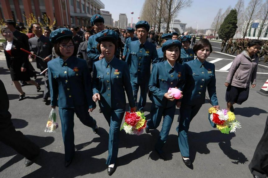 North Korean women in uniform walk along Ryo Myong street after the opening ceremony for a new residential housing project on the street in Pyongyang, on April 13, 2017.