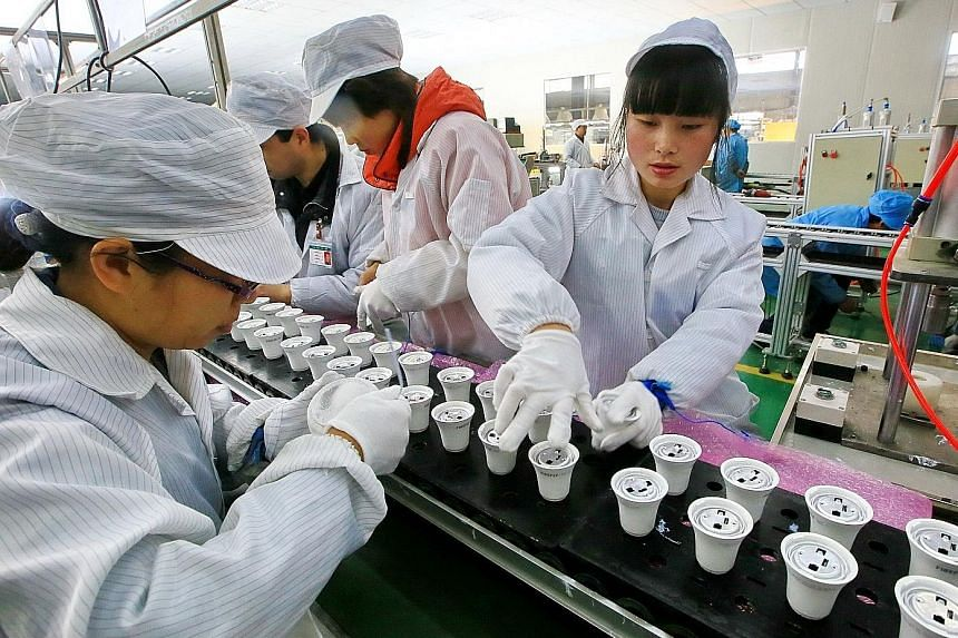 An energy-saving bulb production line in a factory in Suining, Sichuan. A slight uptick in figures in the last three months of 2016 provided signs of stabilisation for China's economy as it expanded 6.7 per cent last year, the slowest rate in a quart