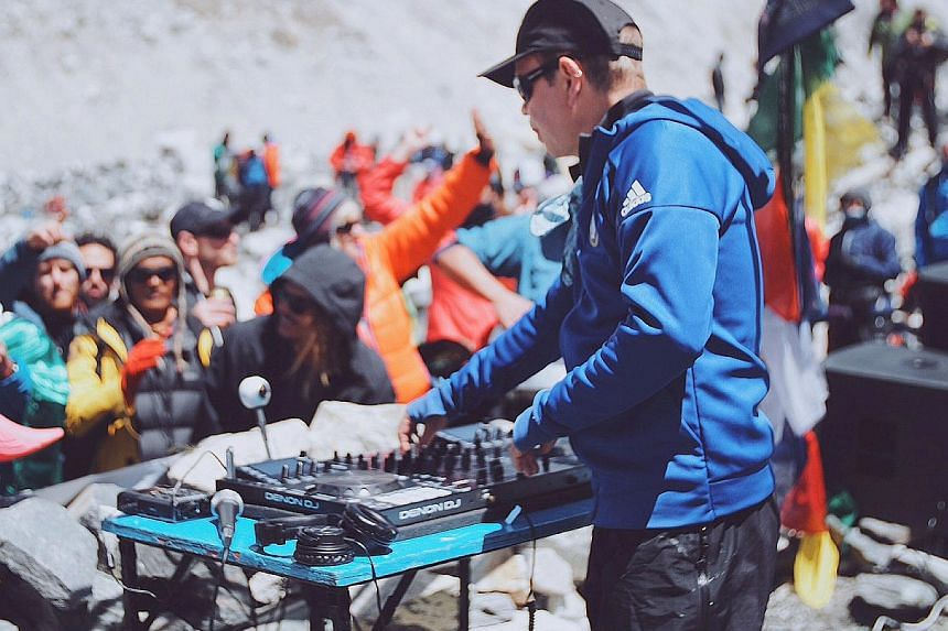 DJ Paul Oakenfold trekked for 10 days (above) to reach Everest base camp and performed on a makeshift stone stage (top) to draw attention to global warming and raise money for charities.