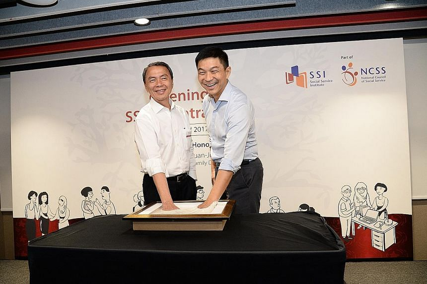 Minister Tan Chuan-Jin (right) is joined by NCSS president Hsieh Fu Hua for the hand-casting ceremony to mark the official opening of the Social Service Institute's new premises at Central Plaza in Tiong Bahru.