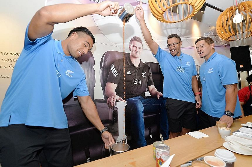 Sione Molia of the New Zealand Sevens side shows his hand-to-eye coordination while learning how to prepare teh tarik as his team-mates cheered him on at Baker & Cook yesterday.