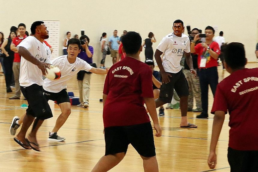 Fiji players in a rugby sevens clinic with 50 students from SportCares' school partners at the OCBC Arena yesterday. After losing three finals this year, the team are rejuvenated by their victory in Hong Kong.