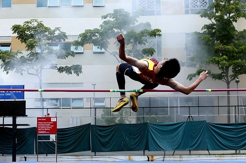Victoria School's Yeo Chengyi in action at the B Division boys' high jump final during the National School Games track and field championship at Bishan Stadium yesterday. With a jump of 1.65m, he finished in 14th position. Schoolmate Kampton Kam won
