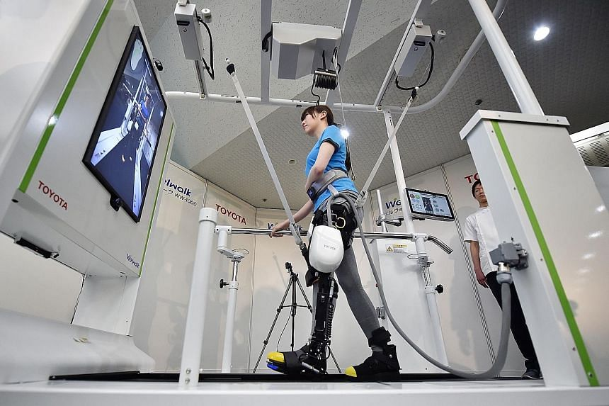 A model showing how the Welwalk WW-1000 robot, developed by Japan's Toyota Motor Corporation, helps in flexing and extending the knee while she walked on a treadmill at a media preview in Tokyo yesterday. Toyota will launch a rental service for the W