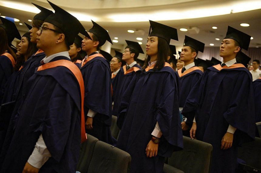 Graduates standing as they listen to the National anthem at the National University of Singapore Commencement ceremony held at the University Cultural Centre on July 7, 2016.