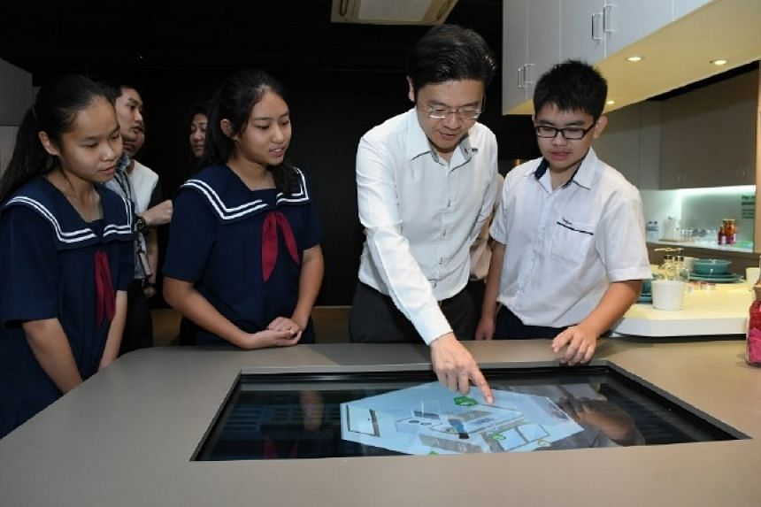 Students from Woodgrove Secondary School sharing information on an interactive multimedia display with Minister Lawrence Wong.