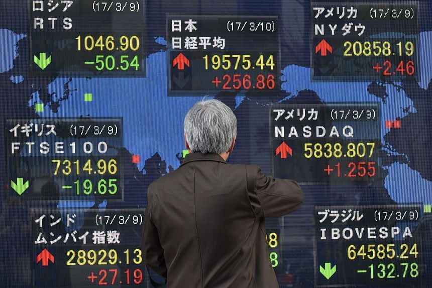 A man looking at an electric quotation board flashing numbers of the world's stock markets in front of a securities company in Tokyo on March 10, 2017.