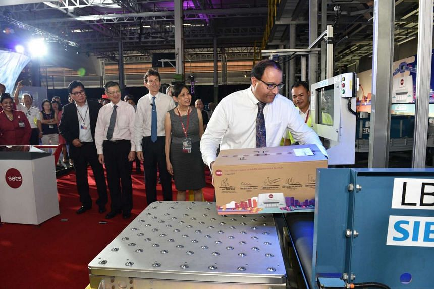 Trade and Industry (Industry) Minister S. Iswaran placing a parcel in the in-feed station at the new Sats e-Commerce AirHub.