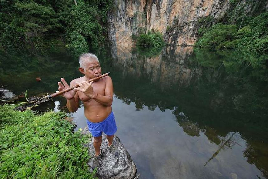 Retiree Tan Eng Bee fills the quarry lake in Bukit Batok Nature Park with music from his Chinese flute every weekend. The granite workers are long gone, but their legacy lives on in the scenic beauty of the cliffs and lakes left behind.