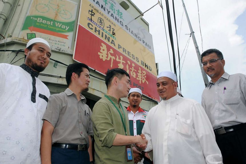 Penang PAS state commissioner Muhammad Fauzi Yusof shaking hands with Nanyang Siang Pau representative Lai Thiem Wah after meeting with the Chinese daily on Tuesday. Earlier that day, PAS members staged a protest against the caricature, deemed to be