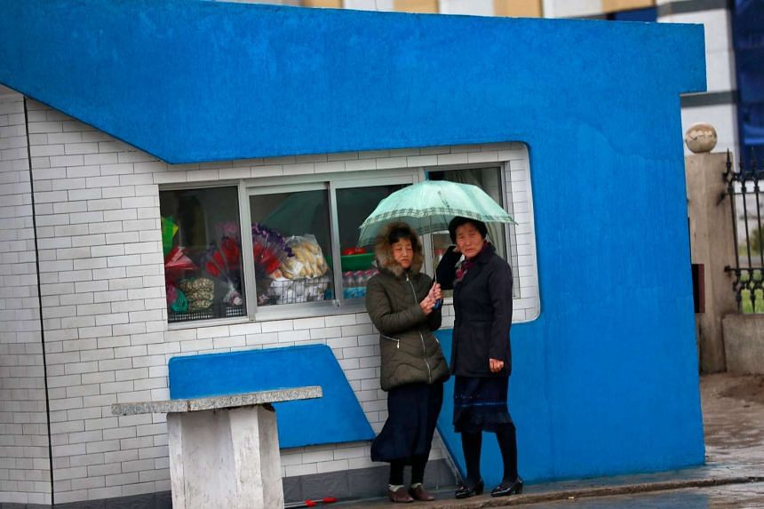 Two women take shelter from the rain in front of a shop in Pyongyang.