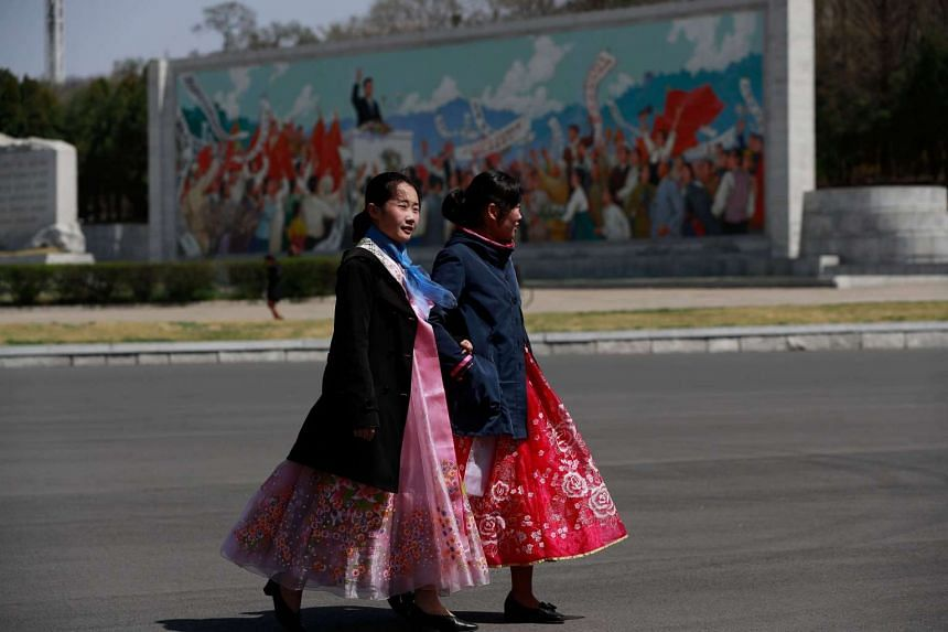 Women return from a rehearsal for 'Day of the Sun' celebrations near the Kim Il Sung Stadium in Pyongyang.
