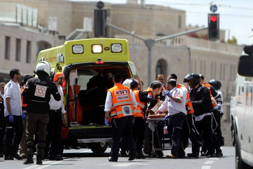 Israeli medics evacuate an injured person following a stabbing attack just outside Jerusalem's Old City, on April 14, 2017.