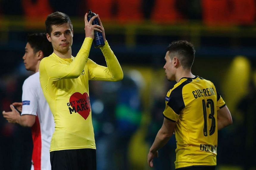 "Dortmund's midfielder Julian Weigl wears a shirt with ""Get well soon, Marc"" on it for his injured teammate, Dortmund's Spanish defender Marc Bartra, who was injured in an attack on their team bus."