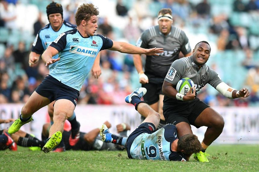 Manasa Mataele (right) of the Crusaders is tackled by Jake Gordon (on ground) and Michael Hooper (second from left) of the Waratahs during a match on April 2.