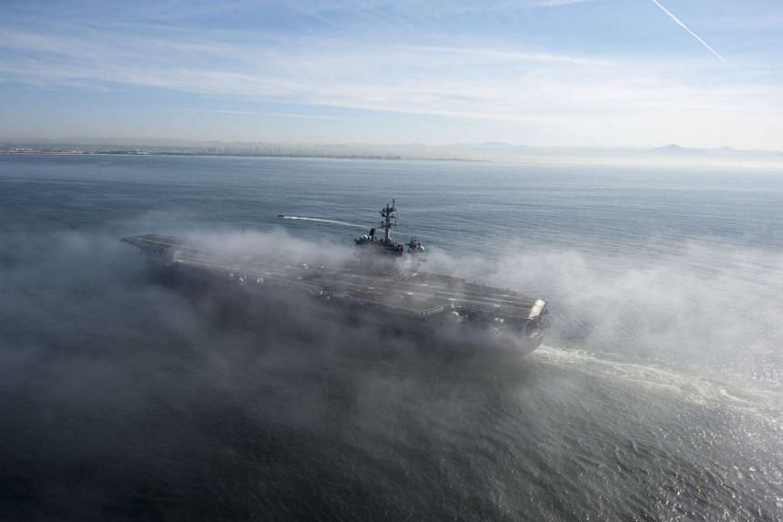 A handout picture of the US Navy Media Content Service, showing aircraft carrier USS Carl Vinson (CVN 70) passing through a fog bank on the Pacific Ocean during a transit to homeport at Naval Air Station North Island, California, US, on April 10, 201