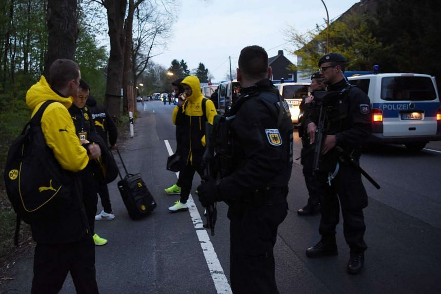 Police escort Borussia Dortmund players after the team bus was damaged by explosions on April 11, 2017.