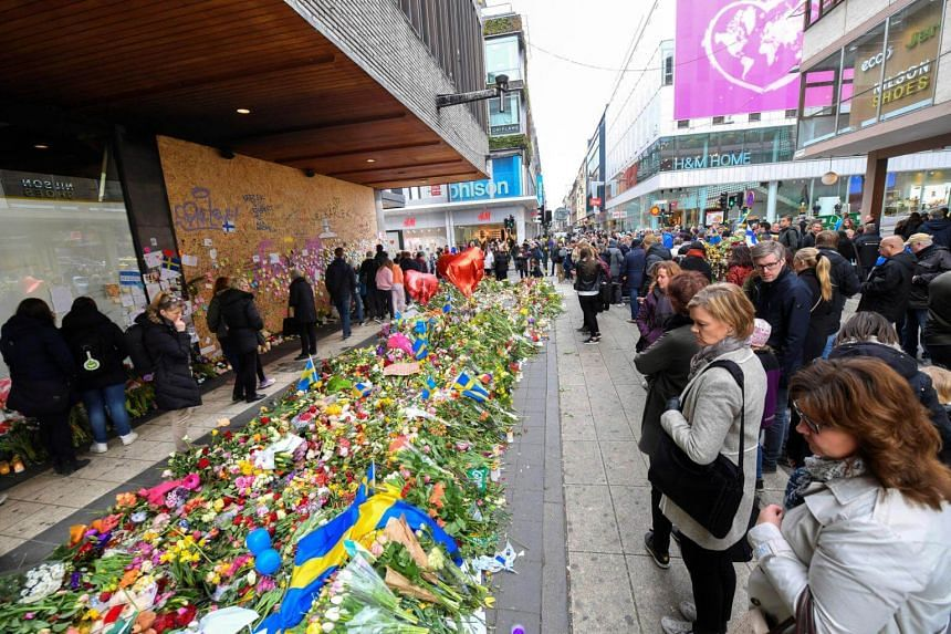 People lay flowers near Ahlens department store, the site of last week's terrorist attack.