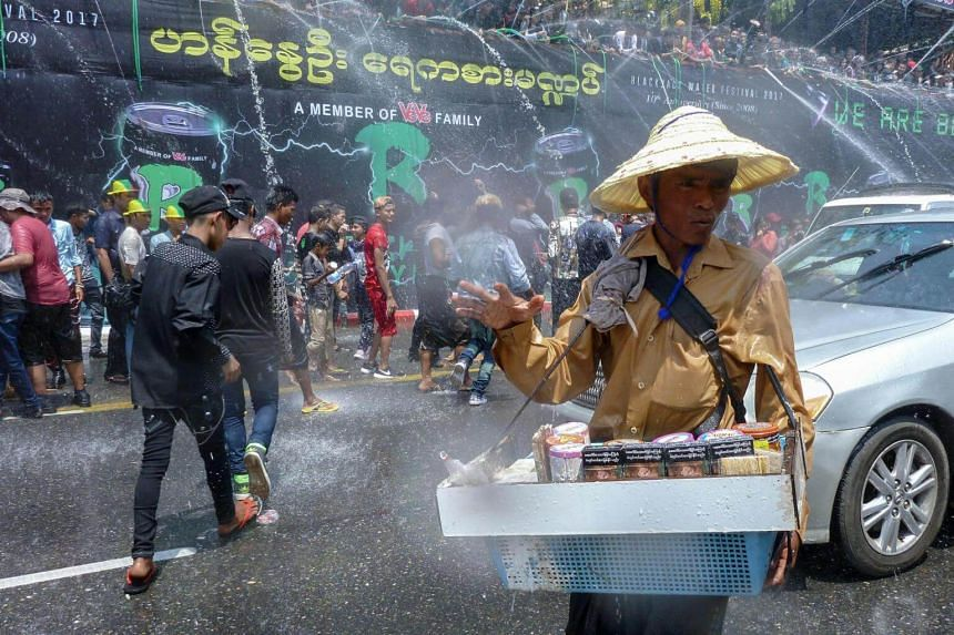 A street vendor offers betel chewing mixes and cigarettes in Yangon, Myanmar, near a crowd celebrating the Buddhist New Year or Thingyan as it is known locally.