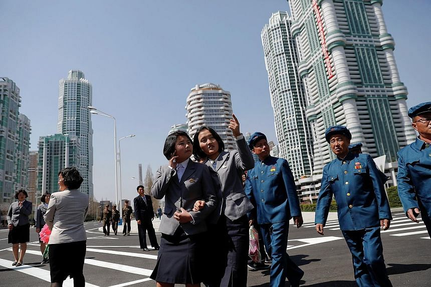 North Koreans checking out the newly opened Ryomyong Street development in Pyongyang yesterday. North Korean leader Kim Jong Un opened the prestige housing project in downtown Pyongyang yesterday, with tens of thousands of citizens looking on. Comple